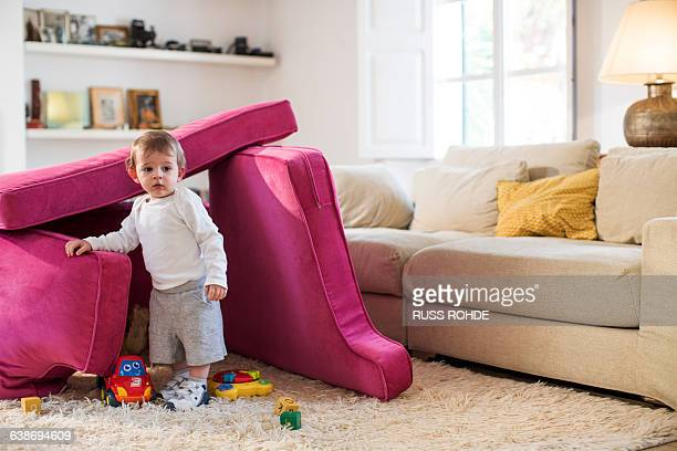 Baby boy playing in fort made from sofa cushions