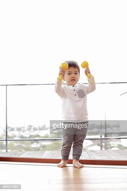 baby boy playing maracas in living room - maraca stock photos and pictures