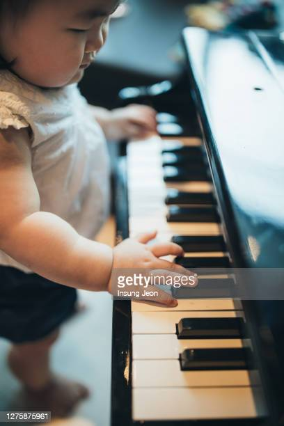 baby boy playing small piano - first occurrence stock pictures, royalty-free photos & images