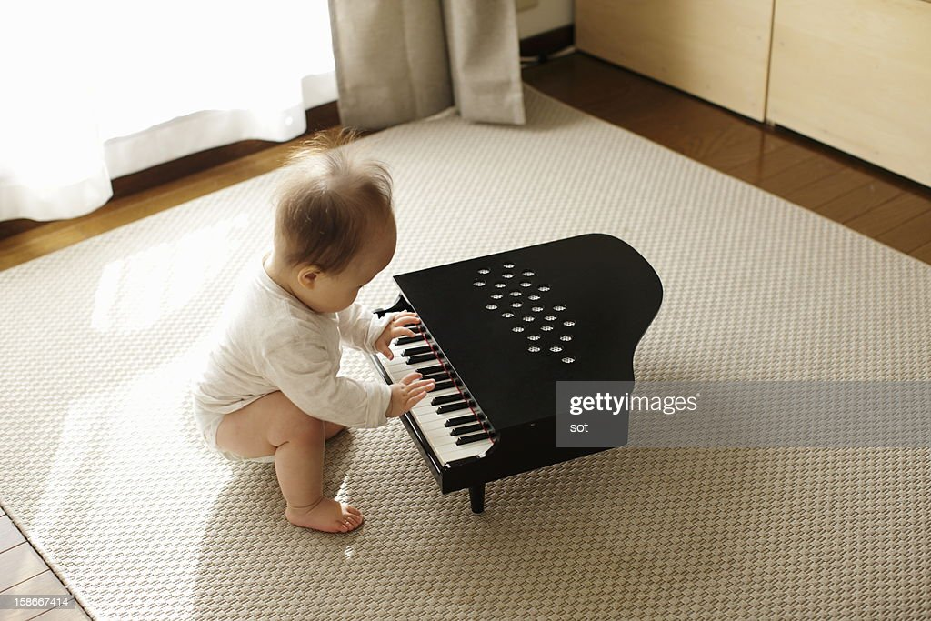 Baby boy playing small piano : ストックフォト