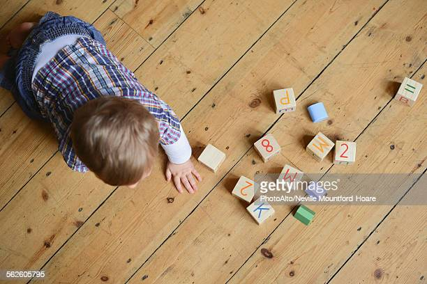 Baby boy playing with abc blocks, overhead view