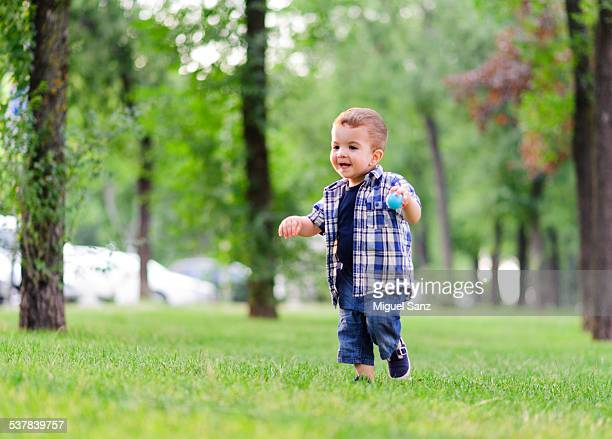 Baby boy playing with ball on grass, Madrid