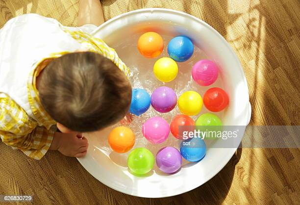 baby boy playing with colorful ball - wash bowl stock pictures, royalty-free photos & images