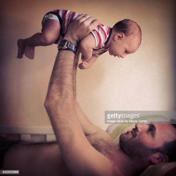 baby boy playing with dad in bed - leanintogether stock pictures, royalty-free photos & images