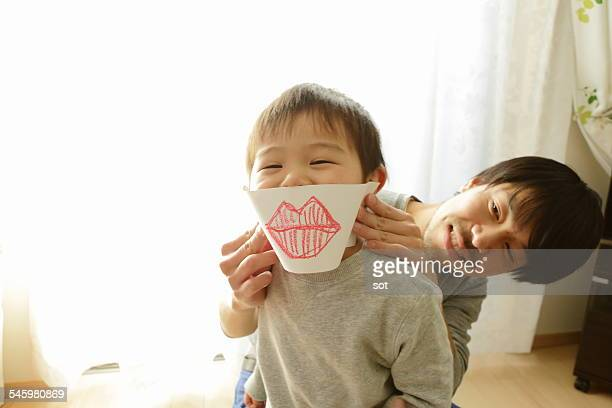 Baby boy playing with father using picture of lips