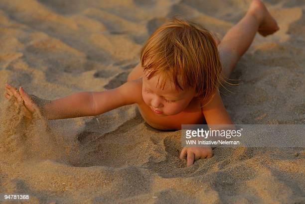 Baby boy playing with sand on the beach, Gokarna, Uttara Kannada, Karnataka, India