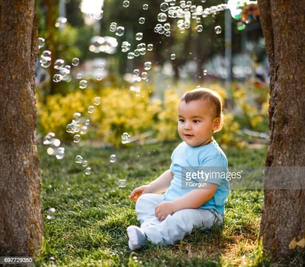 Baby Junge spielt mit Seifenblasen