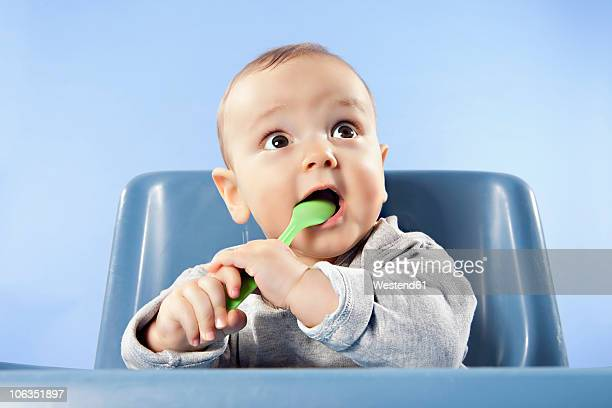 Baby boy playing (6-11 months) with spoon, looking away