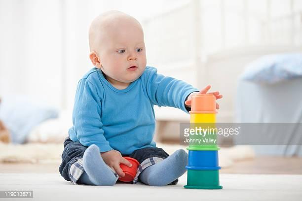 Baby Jungen spielen mit Stapeln Körbchen