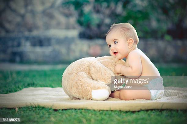 Baby boy playing with teddy bear on the grass