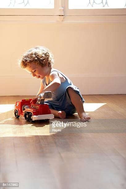 Bebé niño jugando con coche de bomberos de juguete