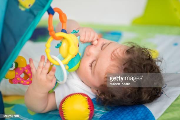 Jungen spielen mit Spielzeug und beißen Kauspielzeug