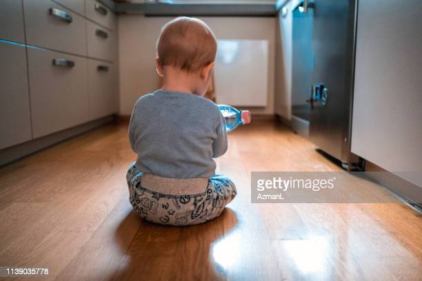 baby boy playing with water bottle on kitchen floor - one baby boy only stock pictures, royalty-free photos & images