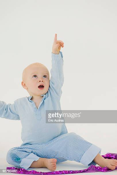 baby boy pointing upward - baby pointing stock photos and pictures