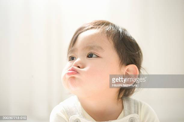 baby boy (18-21 months) pulling face, close-up - 息を止める ストックフォトと画像