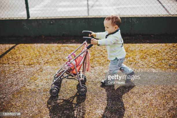 baby boy push doll stroller outdoor.he is wearing casual clothes and pacifier - adult imitation stock pictures, royalty-free photos & images