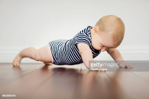 baby boy pushing off of floor at home - vida de bebé fotografías e imágenes de stock