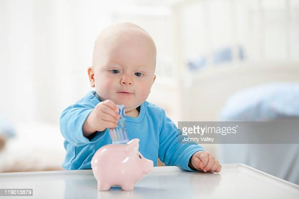 Baby boy putting money in piggy bank