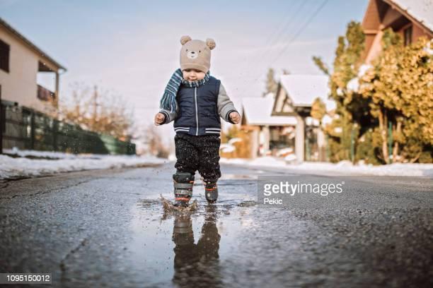 niño corriendo feliz a través de charcos - charco fotografías e imágenes de stock