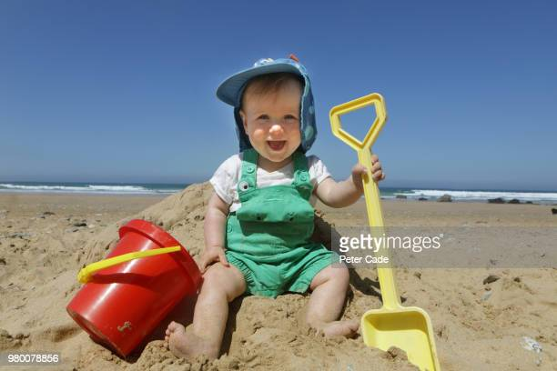 Baby boy sat on beach with bucket and spade