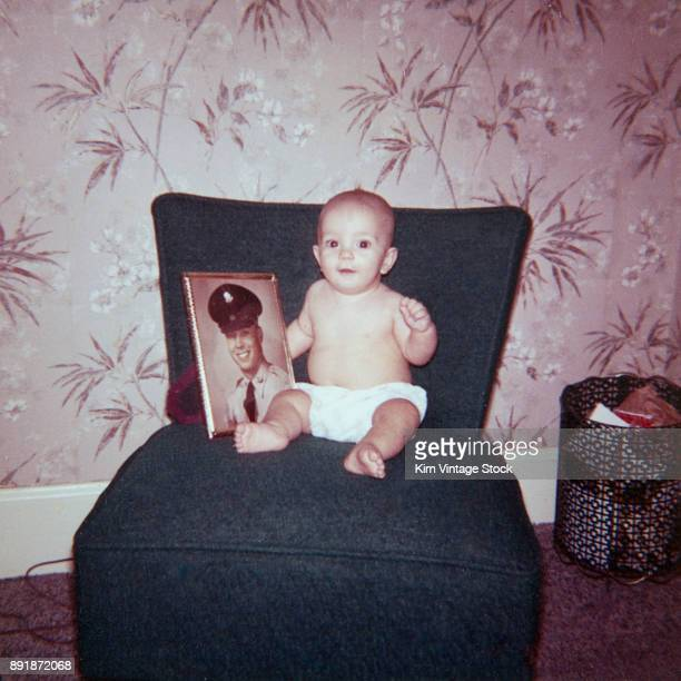 Baby boy sits with a photo of his father, ca. 1961.
