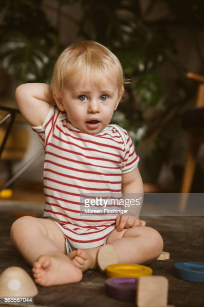 Baby boy sitting at home between wooden toys
