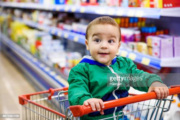 Baby boy sitting at the shopping cart in a supermarket
