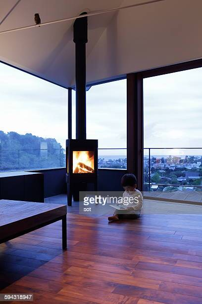 Baby boy sitting by fireplace of  living room