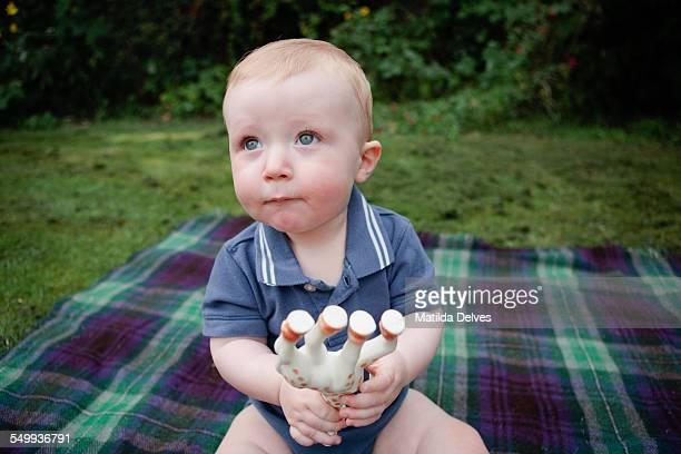 Baby boy sitting in a garden