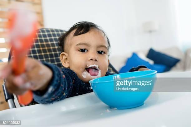 Babyjongen zitten in een kinderstoel en tong uitsteekt