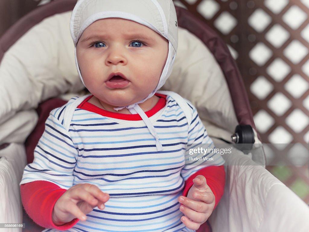 Baby boy sitting in a pram : Stock Photo