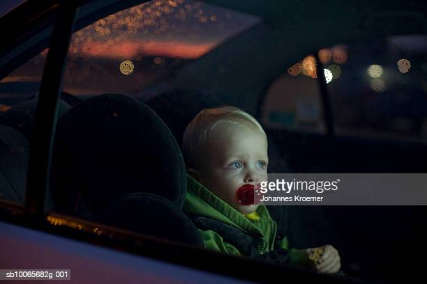 Baby boy (12-18 months) sitting in back seat of car, night
