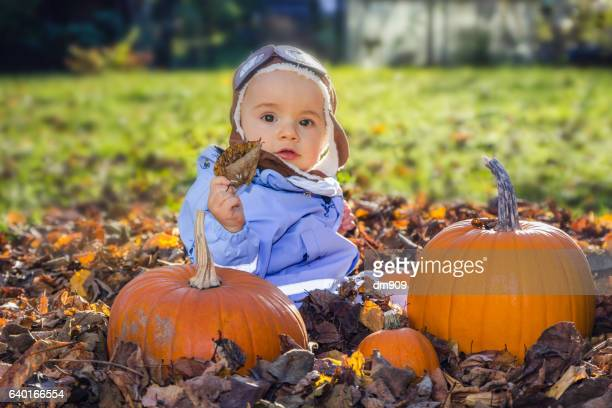 baby boy sitting in backyard with pumpkins