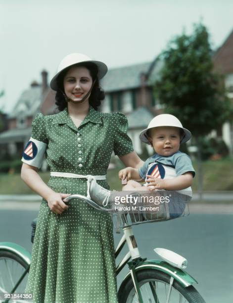 Baby boy sitting in bicycle basket with mother standing besides