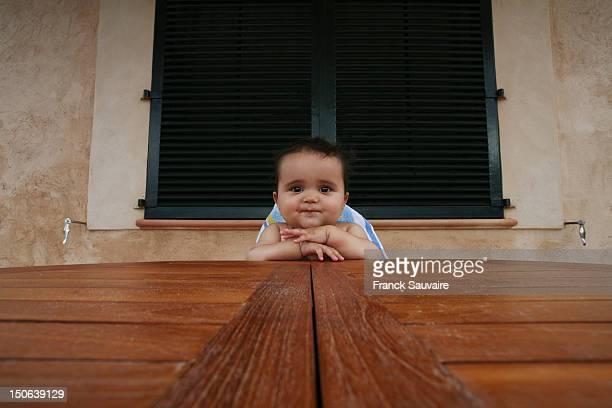 Baby-Jungen in Hochstuhl sitzen am Tisch
