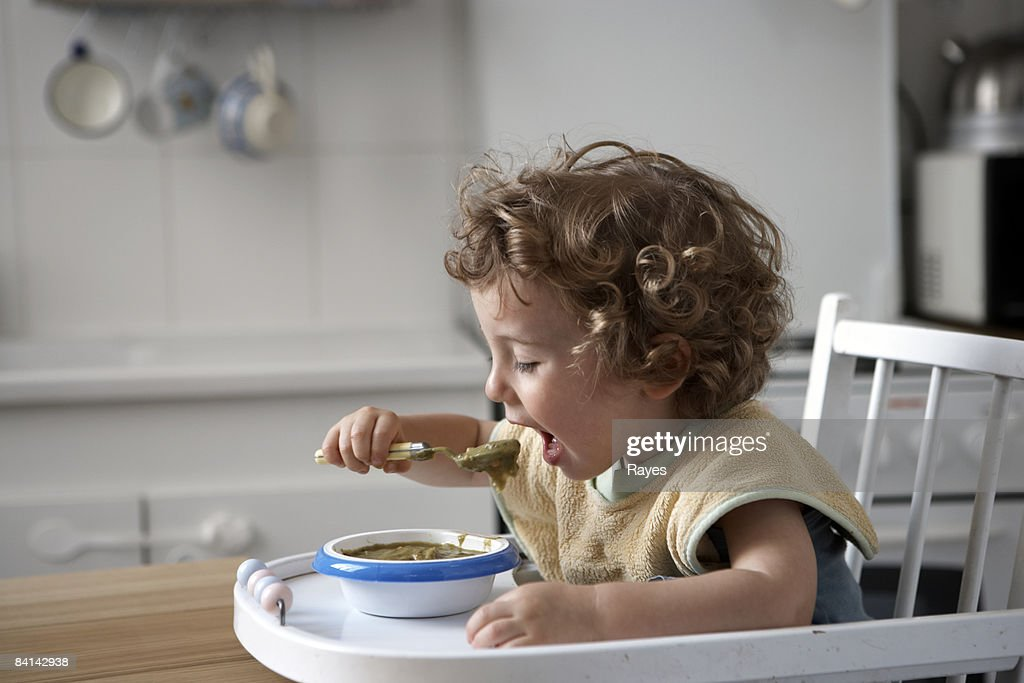 baby boy sitting in high chair feeding himself : Stock Photo