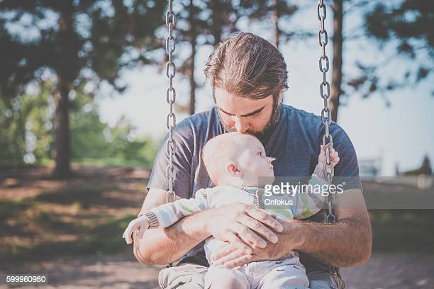 baby boy sitting in playground swing outdoors with dad - baby depression stock pictures, royalty-free photos & images
