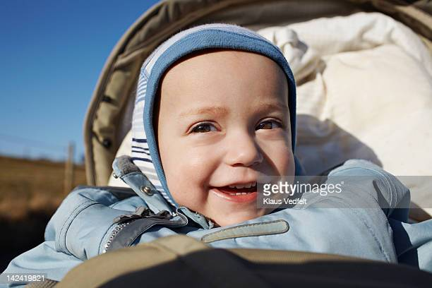 Baby boy sitting in stroller smiling