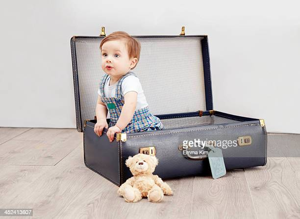 Baby boy sitting in suitcase