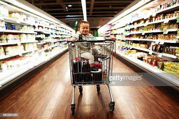 Baby boy sitting in supermarket trolley