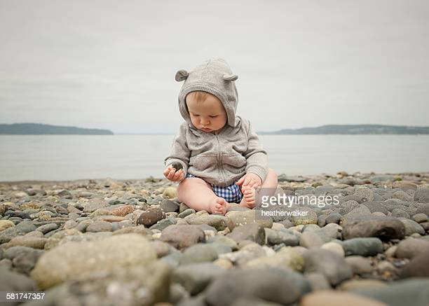 Baby boy sitting on a beach playing with pebbles