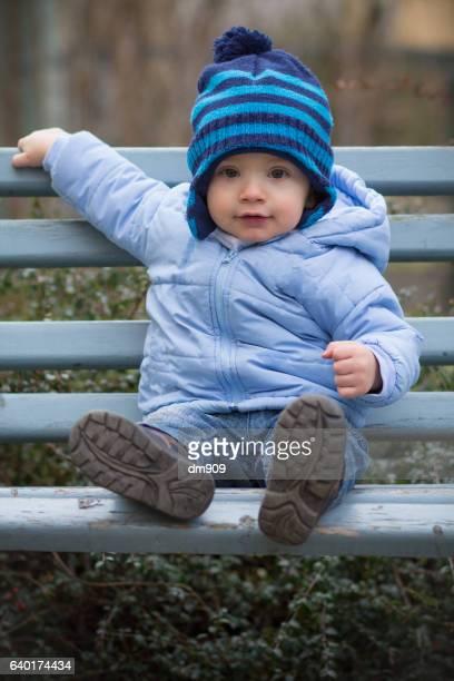 baby boy sitting on a bench