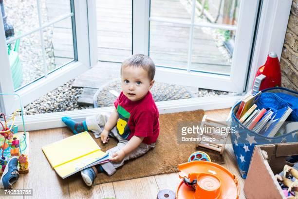 Baby boy sitting on door mat