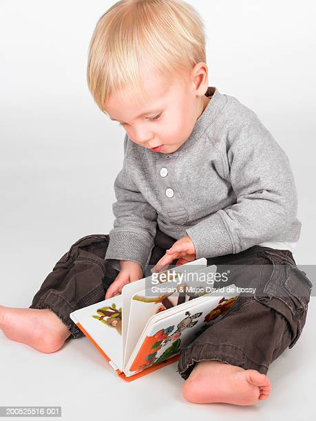 Baby boy (16-24 months) sitting on floor looking at picture book