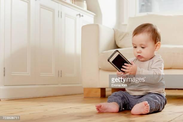 baby boy sitting on floor looking at smartphone - emma white stockfoto's en -beelden