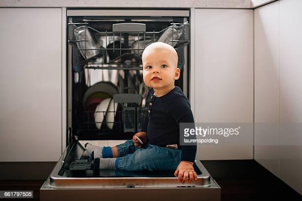 Baby boy sitting on open dishwasher door