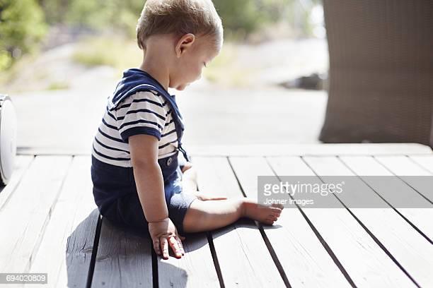Baby boy sitting on porch