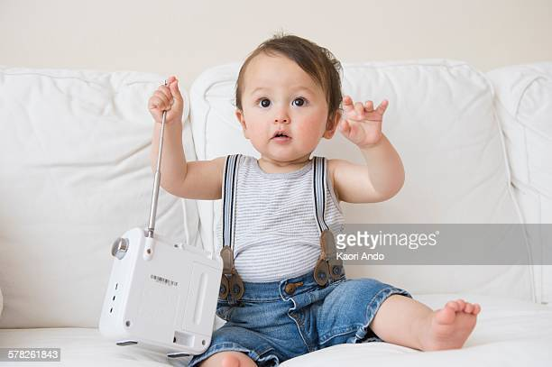 Baby boy sitting on sofa playing with transistor radio aerial