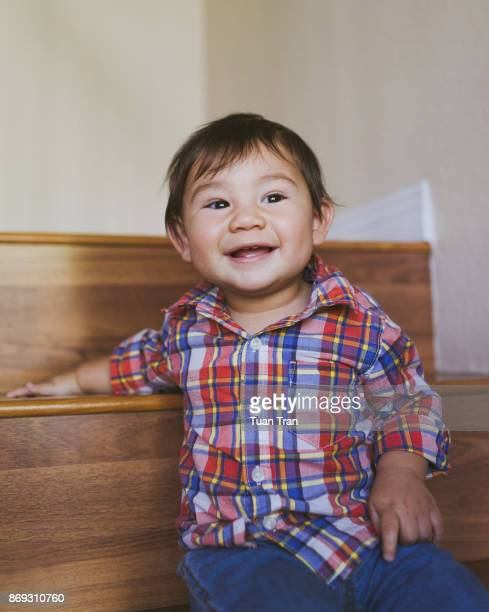 Baby boy sitting on stairs