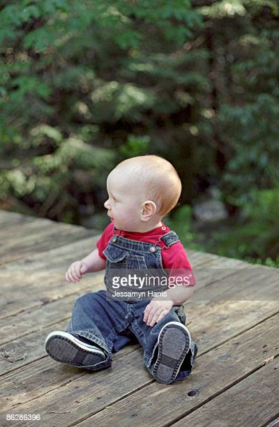 baby boy sitting on wooden deck - jessamyn harris stock pictures, royalty-free photos & images